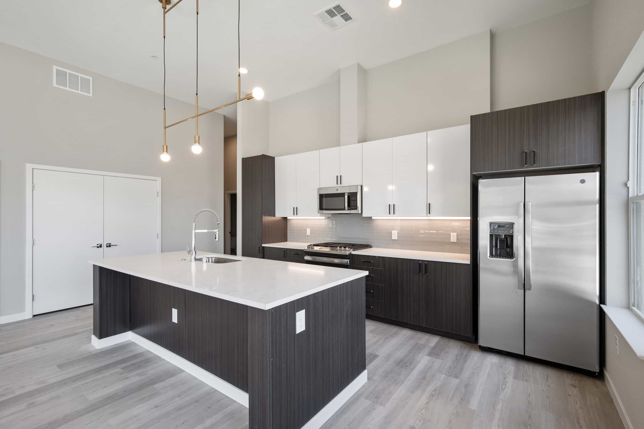 Auric Symphony Park apartment kitchen with white quartz countertops and stainless steel appliances