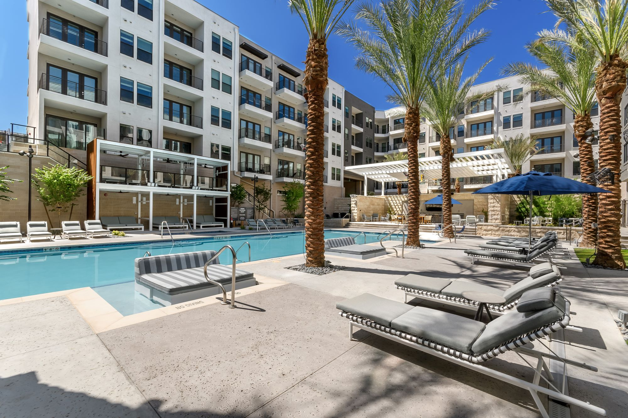 resort-style pool and spa area with lounge chairs at Auric Symphony Park